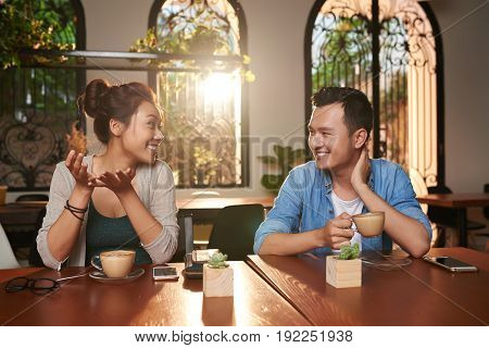 Portrait of cheerful Asian couple chatting in cafe and smiling while on date