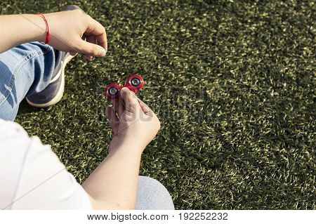 closeup of a young caucasian man playing with a red fidget spinner on nature background. Popular spinner gadget in 2017.