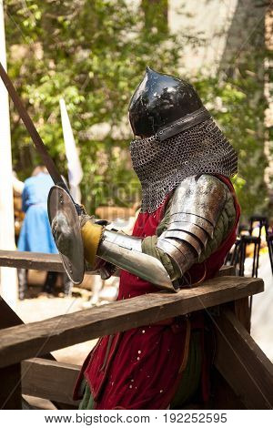 Middle ages period costume at knight tournament. Medieval historical reenactment - a man wearing metal helmet and armor suit holding a sword and a shield