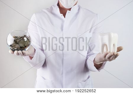 Closeup portrait healthcare professional dentist holding piggy bank and tooth isolated indoors dentist's office background. Health savings financial concept. Medical insurance medicare reimbursement. Happy male doctor dentist with piggy bank and Tooth pro