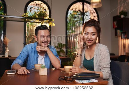 Portrait of young Asian man flirting with beautiful woman in cafe