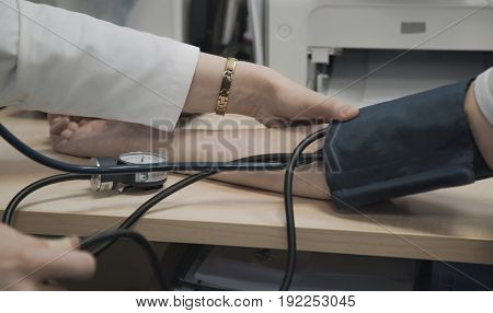 Doctor measures blood pressure of patient in hospital