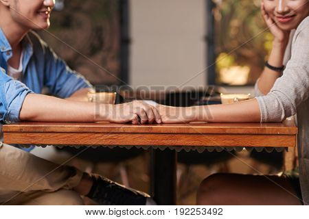 Closeup of young Asian couple holding hands affectionately on date in cafe