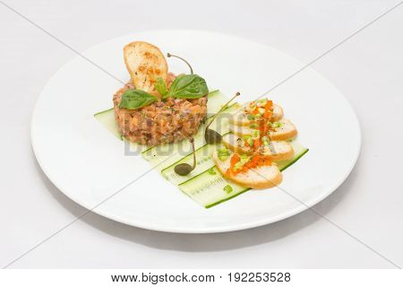 Salmon tartare with toasts on a white plate on white background with green leaves and capers
