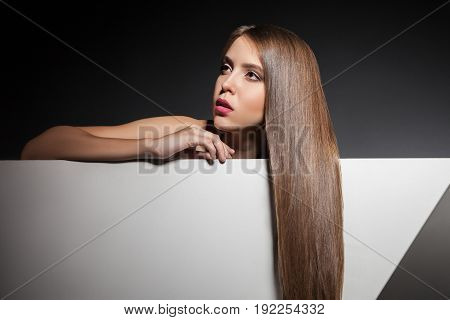 Sensual young woman with shining brunette hair