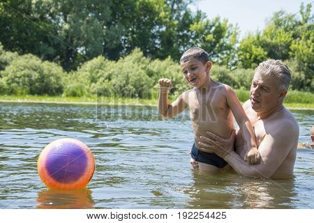 In summer on a bright sunny day on the river grandfather teaches his grandson to swim and plays with him with the ball.