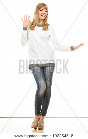 Fashion. Young blonde fashionable woman jeans pants white long-sleeved shirt. Female model posing isolated studio shot