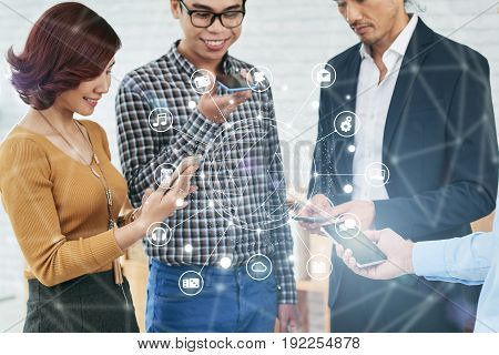 Group of cheerful Asian colleagues with smartphones in hands gathered together in office lobby, collage