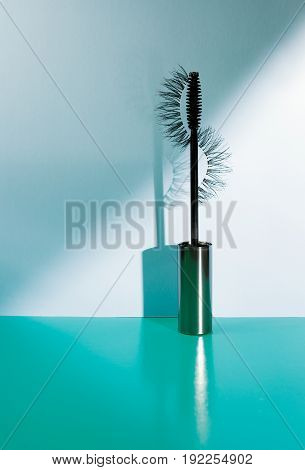 Applicator mascara and false eyelashes with drop shadow on sea-green background.