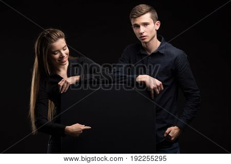 Young happy couple portrait of a confident businessman showing presentation, pointing paper placard black background. Ideal for banners, registration forms, presentation, landings, presenting concept.