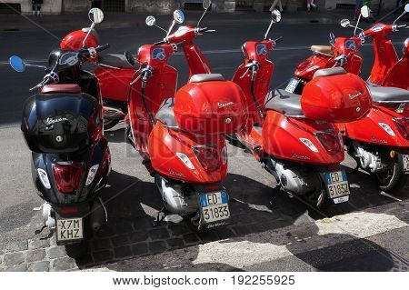 Rome Italy - June 9 2017: A row of red Vespa scooters is parked along Via Cavour where you rent a scooter.