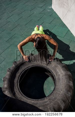 Top view of young woman in bright sexy leggings with pretty athlete muscular body doing push ups exercise on big tire. Cross training urban area street gym city workout routine healthy lifestyle.