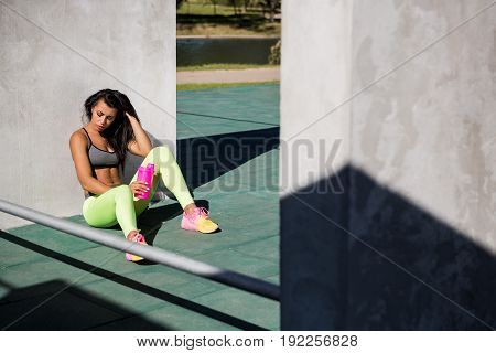 Beautiful young girl with long legs in bright sexy leggings with pretty athlete muscular body sit with protein shaker. Cross training urban area street gym city exercise routine healthy lifestyle.