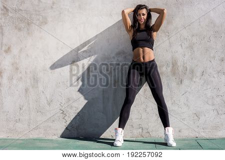 Young beautiful strong lady with pretty athlete muscular body stand in front of gray wall and smile to camera. Cross training urban area street gym city workout exercise routine healthy lifestyle.
