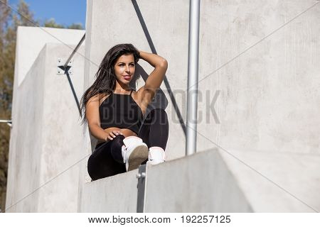Beautiful young girl with long legs in black sexy leggings with pretty athlete muscular body rest after yoga. Cross training urban area street gym city exercise routine healthy lifestyle.
