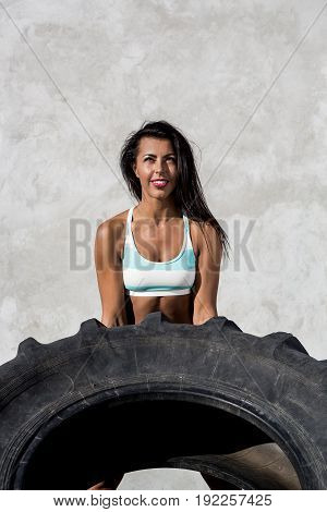 Portrait of a young woman in sexy shorts with pretty athlete muscular body lift up big heavy tire with happy smile. Cross training urban area street gym city exercise routine healthy lifestyle.