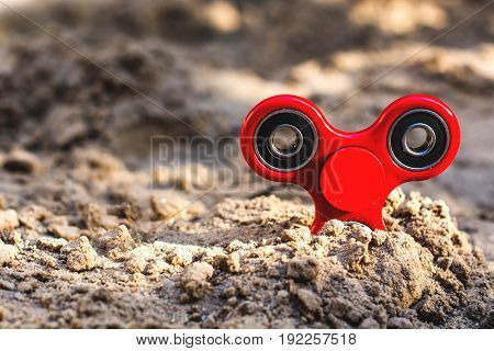 Popular red spinner gadget in 2017 against the background of sand. Modern red plastic spinner fidget game for young people.