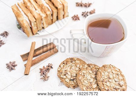 White cup with tea homemade cookies with cereals Viennese waffles with cream filling cinnamon sticks anise stars on a white lace tablecloth