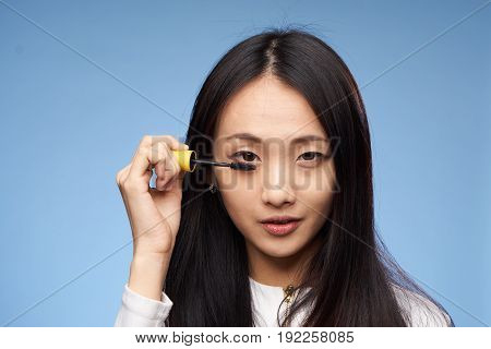 Beauty, make-up, girl paints eyelashes, woman on blue background, asian.