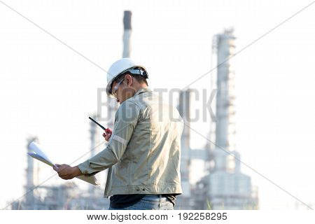 The man engineer reading the drawing paper construction for plan work at power plant Thailand. Engineer Concept.