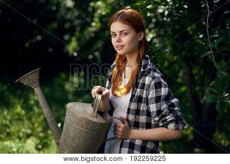 Girl in the garden, watering can, gardener, gardening, dacha season, red-haired girl.