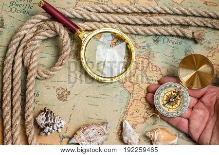 Old vintage retro compass magnifying glass on ancient world map. Vintage still life. Travel geography navigation concept background
