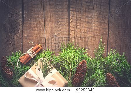 Natural Christmas New Year background. Coniferous branches with cones on old wooden boards. Toned