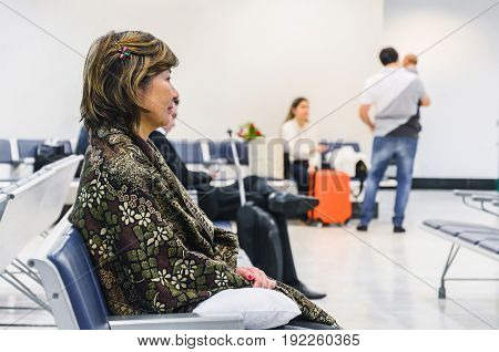 Woman waiting seated on the airport's departure lounge for her flight with some blurred people on background.