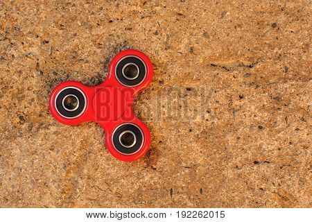 Top view of the popular red spinner gadget in 2017 on a concrete background. popular red fidget spinner toy