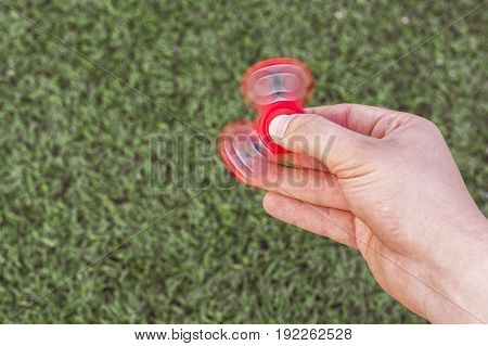 Closeup of a young caucasian man playing with red fidget spinner on f the soccer (football) artificial field. Popular gadget in 2017