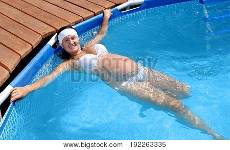 Young smiling pregnant woman swimming in the pool.