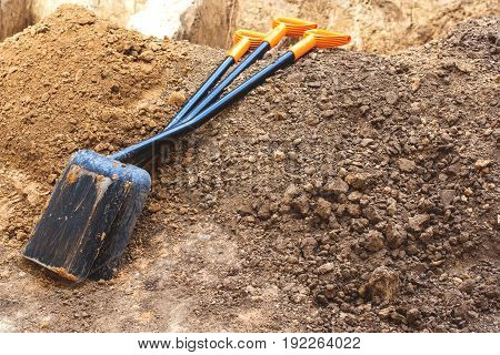 The tools of the shovel lie on the brown ground