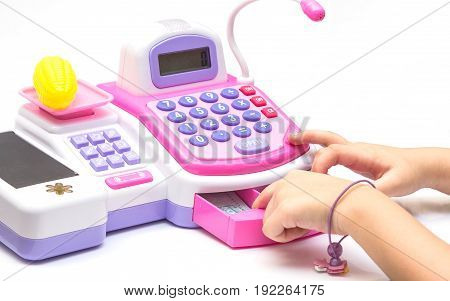 Little girl fingers pressing toy calculator on white background