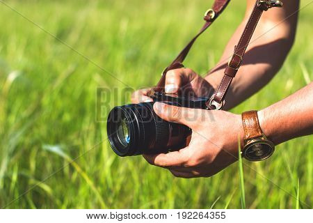 The digital camera in a hand. Male hands with camera take photo of green grass