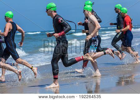 Kijkduin The Hague the Netherlands - 17 June 2017: Kijkduin cross triathlon athletes running into the sea for swimleg