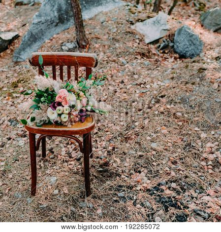 Beautiful wedding bouquet on an old brown chair standing outside in park. Square