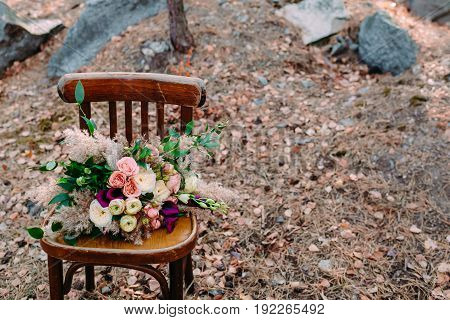 Beautiful wedding bouquet on an old brown chair standing outside in park. Autumn wedding