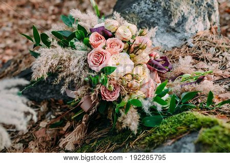 Beautiful wedding bouquet consisting of different flowers lying on a stone in the park. Autumn wedding. Outside