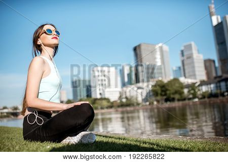Young woman doing yoga near the river with great view on Frankfurt city