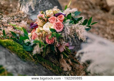 Beautiful wedding bouquet consisting of different flowers lying on a stone in the park. Autumn wedding. Close-up