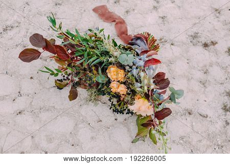 Gorgeous wedding bouquet consisting of different flowers lying on a stone in the park. Bunch of flowers. Close-up