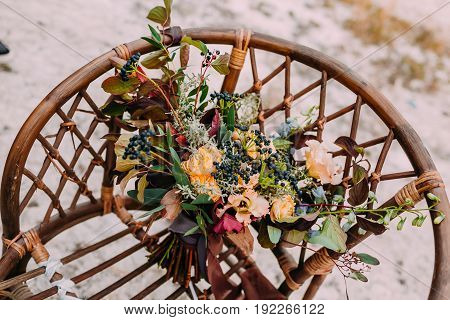 Beautiful wedding bouquet consisting of different flowers lying on an old brown chair. Bunch of flowers. Vertical