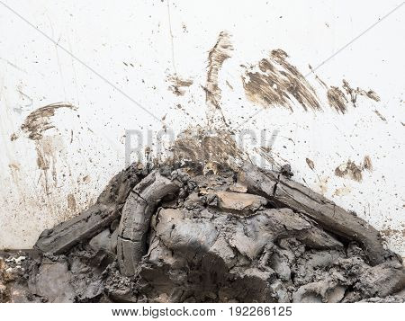 Clay pile from the construction site near the white concrete wall of the house which expanding.