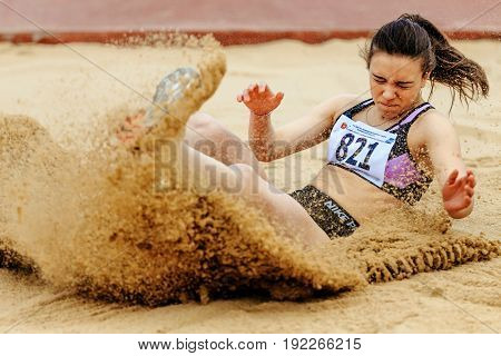 Chelyabinsk Russia - June 4 2017: woman athlete landing in sand long jump during UrFO Championship in athletics