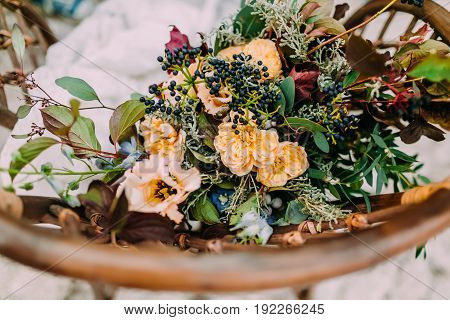 Beautiful wedding bouquet consisting of different flowers lying on an old brown chair. Bunch of flowers. Close-up