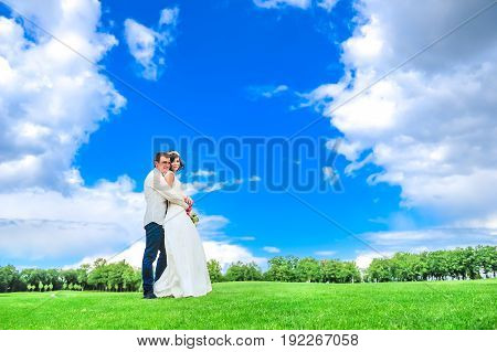 Young And Handsome Newlyweds On A Walk In The Park: Groom Hugs The Bride