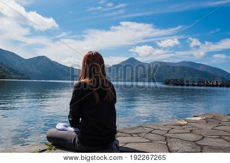 A Woman sitting alone Lake and blue sky background.