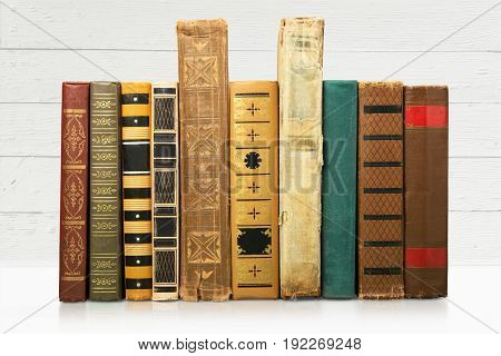 Old antique worn books lined up on a shelf.