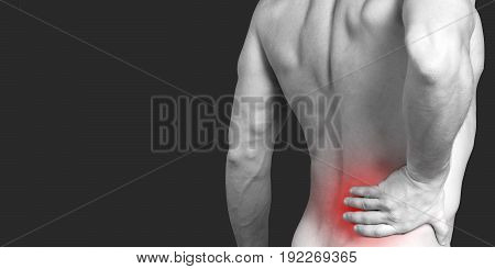 Close up on man's back showing pain area in red. Black background with copy space. Healthcare concept. Black and white.