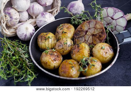 Fried Potatoes In A Pan With Garlic And Thyme.